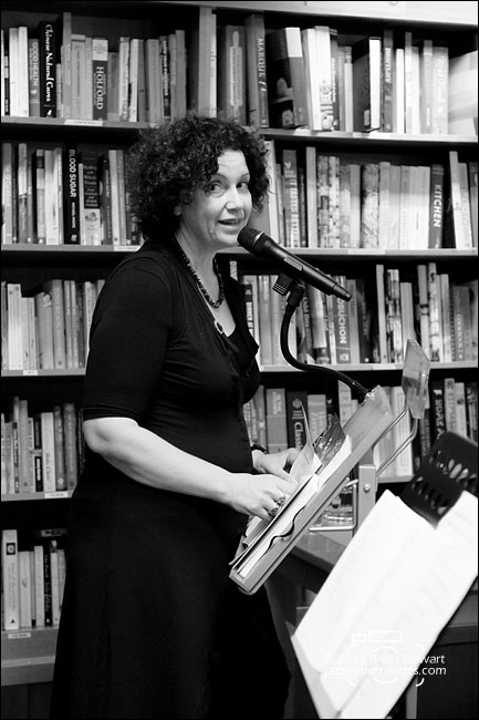Black and white photo of a woman standing in front of bookshelf, speaking into microphone and looking at the camera